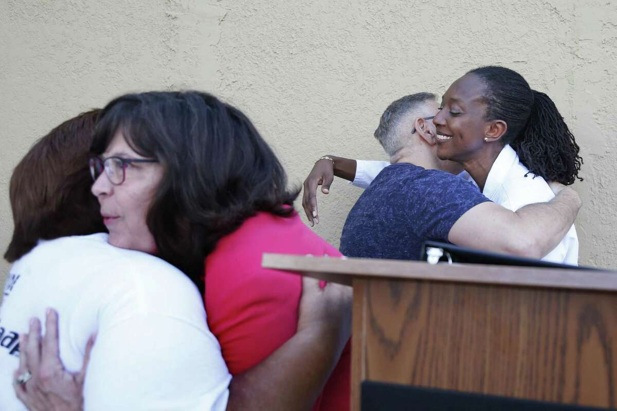 SAAF CEO Cynthia Nelson (left) and Dr. Waridibo Allison (right), who heads the clinic, hug Mary Helen Gloria and Carlos Carmona on Friday as the San Antonio AIDS Foundation opens an HIV outpatient clinic with a pharmacy on the East Side.