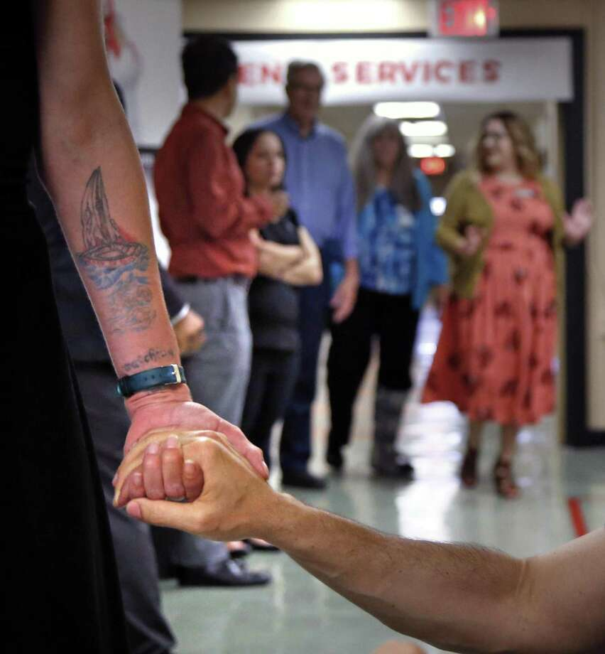 A former patient holds hands with Andrea Moutria-Nino, Director of Prevention at an AIDS Foundation HIV outpatient clinic on the East Side in November. The former patient is doing great. Photo: Ron Cortes /
