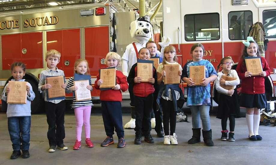 The winners of the 2017 OFire Prevention MonthO Poster Contest get their photo taken holding their awards with Sparky the firehouse mascot during a ceremony at the Troy Central Fire House on Friday, Nov. 17, 2017 in Troy, N.Y. (Lori Van Buren / Times Union) Photo: Lori Van Buren / 20042172A