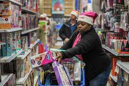 NyAsia Morrison of the Lansingburgh Dunkin Donuts gathers gifts during the shopping spree funded by Dunkin Donuts locally for the Marine Corps Reserve Toys for Tots Train Friday Nov. 17, 2017 at the Toys R Us store in Colonie, N.Y.    (Skip Dickstein/ Times Union)