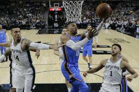 Oklahoma City Thunder guard Russell Westbrook (0) drives to the basket past San Antonio Spurs defenders Danny Green (14) and Kyle Anderson (1) during the first half of an NBA basketball game, Friday, Nov. 17, 2017, in San Antonio. (AP Photo/Eric Gay)