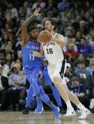 San Antonio Spurs center Pau Gasol (16) drives around Oklahoma City Thunder forward Paul George (13) during the first half of an NBA basketball game, Friday, Nov. 17, 2017, in San Antonio. (AP Photo/Eric Gay)