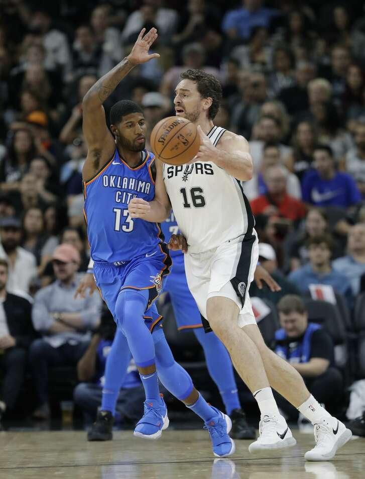 San Antonio Spurs center Pau Gasol (16) drives around Oklahoma City Thunder forward Paul George (13) during the first half of an NBA basketball game, Friday, Nov. 17, 2017, in San Antonio. (AP Photo/Eric Gay)