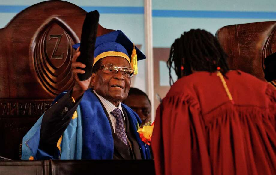In his first public appearance Friday since the military put him under house arrest this week. Zimbabwe President Robert Mugabe, left, presides over a graduation ceremony at Zimbabwe Open University. Photo: Ben Curtis, STF / Copyright 2017 The Associated Press. All rights reserved.