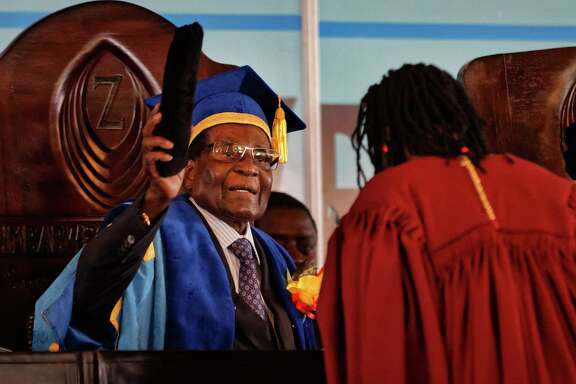 In his first public appearance Friday since the military put him under house arrest this week. Zimbabwe President Robert Mugabe, left, presides over a graduation ceremony at Zimbabwe Open University.