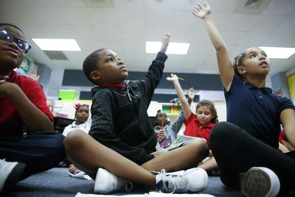 Outley Elementary third grader Antwon Patrick, 9, center, participates in a lesson with his classmates Wednesday, Oct. 4, 2017 in Houston. Patrick, along with 19 other students, started attending Outley after they were displaced by Hurricane Harvey. ( Michael Ciaglo / Houston Chronicle)
