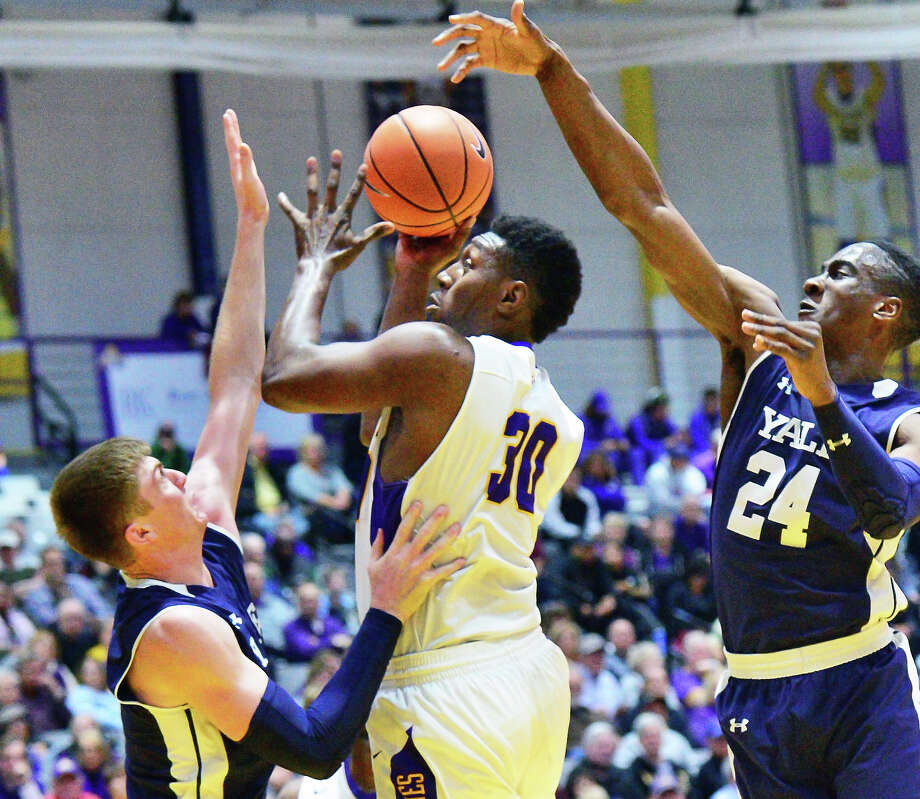 UAlbany's #30 Travis Charles goes to the hoop despite being double teamed by Yale's #4 Noah Yates, left,and #24 Miye Oni, right, during Friday night's game Nov. 17, 2017 in Albany, NY.   (John Carl D'Annibale / Times Union) Photo: John Carl D'Annibale / 20042113A