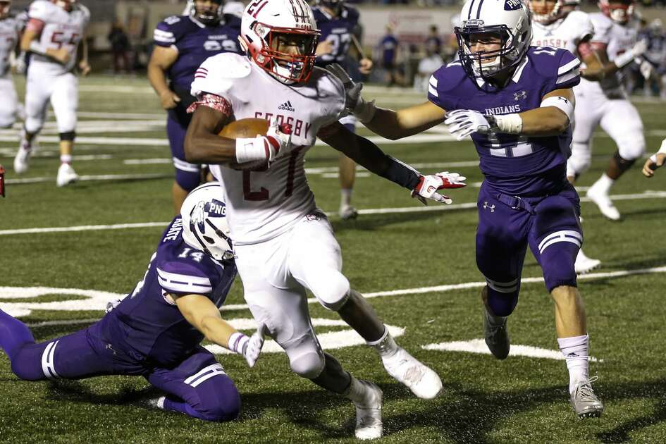 Crosby running back Craig Williams (21) runs between Port Neches-Groves defensive backs Camron Abate (14) and Zane Hernandez (17) during the third quarter of a Class 5A bi-district playoff football game at Stallworth Stadium on Friday, Nov. 17, 2017, in Baytown. Port Neches-Groves advanced in the playoffs with a 72-69 win. ( Brett Coomer / Houston Chronicle )