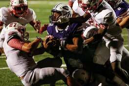 Port Neches-Groves quarterback Roschon Johnson dives into the end zone over Crosby linebacker Hunter Bailey (27) for a 2-yard touchdown, and game winning run, during the fourth quarter of a Class 5A bi-district playoff football game at Stallworth Stadium on Friday, Nov. 17, 2017, in Baytown. Port Neches-Groves advanced in the playoffs with a 72-69 win. ( Brett Coomer / Houston Chronicle )