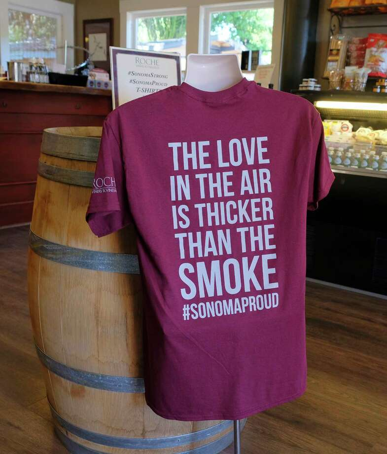 In this photo taken Saturday, Oct. 28, 2017, a t-shirt referencing the recent wildfires is shown for sale in the tasting room at Roche Winery and Vineyards in Sonoma, Calif. The impact the wildfires had on the wine industry was minimal overall, but many face challenges making up for losses sustained during closures at the busiest time of year and now convincing people to revisit. (AP Photo/Eric Risberg) Photo: Eric Risberg, STF / Copyright 2017 The Associated Press. All rights reserved.