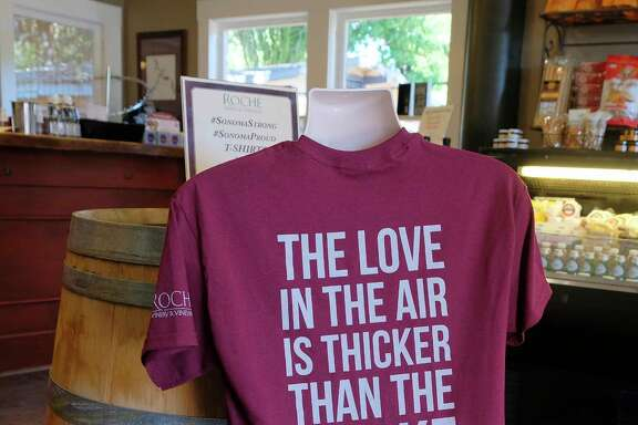 In this photo taken Saturday, Oct. 28, 2017, a t-shirt referencing the recent wildfires is shown for sale in the tasting room at Roche Winery and Vineyards in Sonoma, Calif. The impact the wildfires had on the wine industry was minimal overall, but many face challenges making up for losses sustained during closures at the busiest time of year and now convincing people to revisit. (AP Photo/Eric Risberg)
