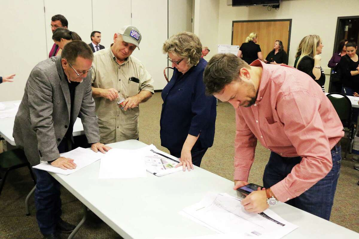 Don Jeanes (red shirt) looks over the maps while officials answer questions from area residents concerning the acquisition of land.