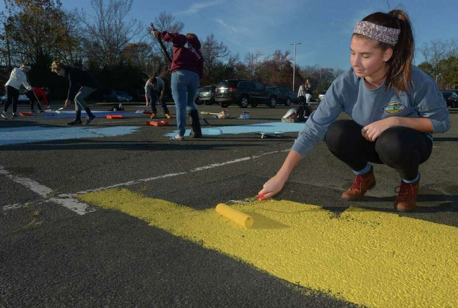 As part of a senior class fundraiser developed by class president Kristen Carrano, right, seniors at Brien McMahon High School paint their parking spaces Friday, November 17, 2017, at the school in Norwalk, Conn. The new tradition will be passed on to future classes. Photo: Erik Trautmann / Hearst Connecticut Media / Norwalk Hour