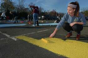 As part of a senior class fundraiser developed by class president Kristen Carrano, right, seniors at Brien McMahon High School paint their parking spaces Friday, November 17, 2017, at the school in Norwalk, Conn. The new tradition will passed on to future classes.