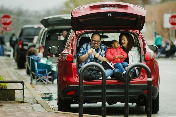 Nick Eisentraut, Cailyn Eisentraut, 2, and Nikki Eisentraut laugh together as they sit in the trunk of their car and wait for the Santa Parade to begin Saturday on Ashman Street. (Katy Kildee/kkildee@mdn.net)
