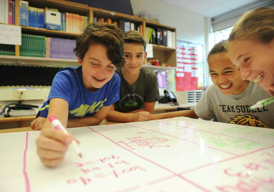 Students, from left, Phillip Vijev, John Sarubbi, Mackenzie Nelson and Makenzie Johnson, work together on a project during seventh-grade math class at Western Middle School in Greenwich on  Oct. 24 . Photo: Tyler Sizemore / Hearst Connecticut Media / Greenwich Time