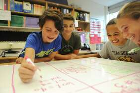 Students, from left, Phillip Vijev, John Sarubbi, Mackenzie Nelson and Makenzie Johnson, work together on a project during seventh-grade math class at Western Middle School in Greenwich on  Oct. 24 .