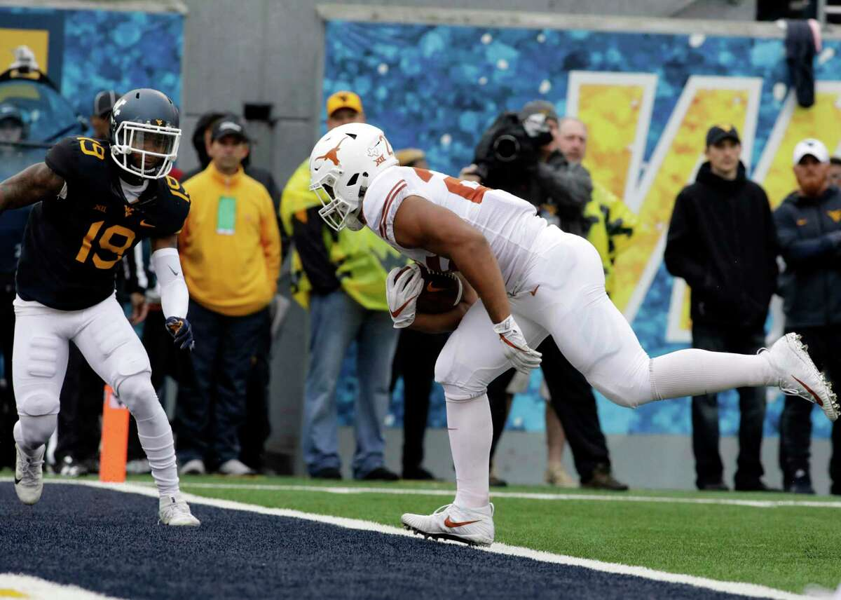 Texas running back Chris Warren III (25) runs into the end zone for a touchdown during the first half of an NCAA college football game against West Virginia, Saturday, Nov. 18, 2017, in Morgantown, W.Va. (AP Photo/Raymond Thompson)