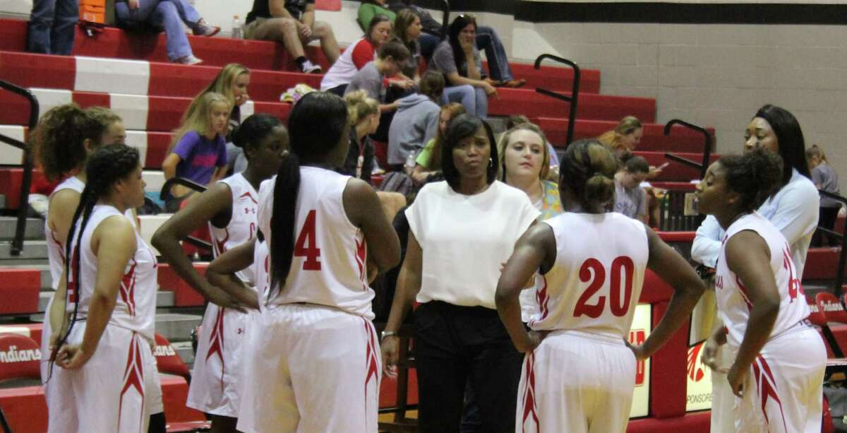 Lady Indians Coach Shiakiea Carter discusses strategy with her team during a time out.