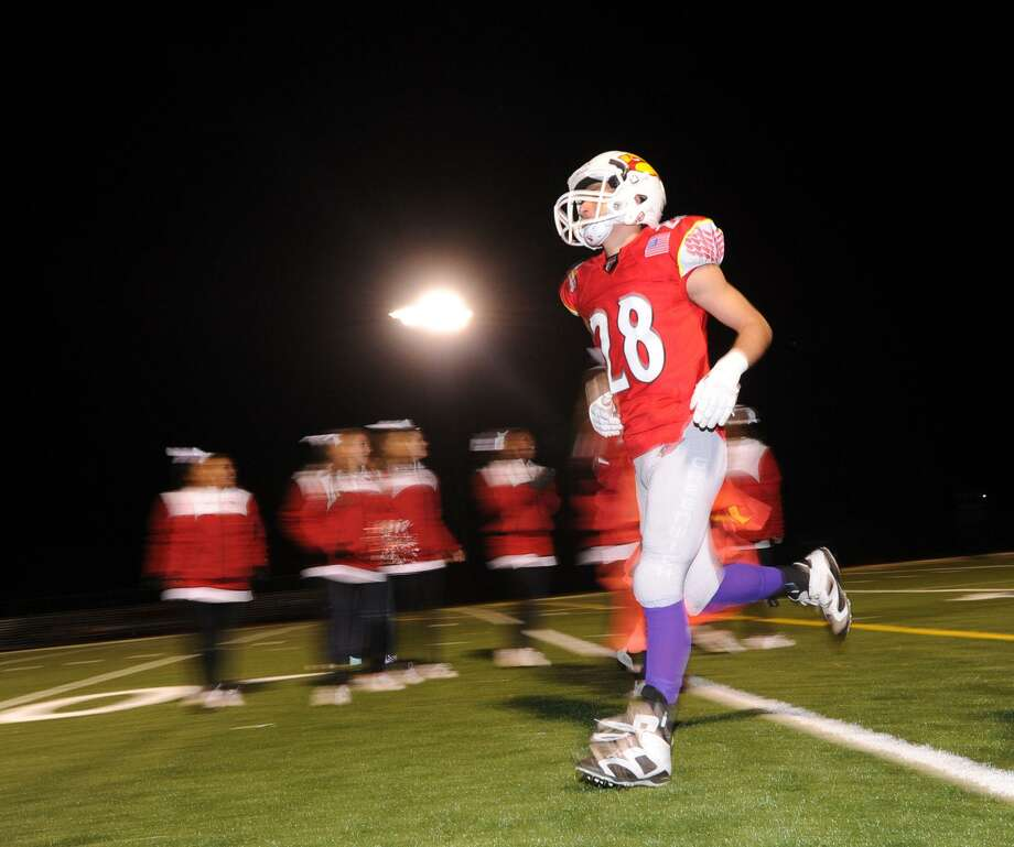 A Greenwich High football player takes to the field beneath the lights at Cardinal Stadium in Greenwich, Conn., Friday night, Oct. 28, 2016. With this year's later school day, and restrictions on use of lights at the school, darkness has become a problem for fall teams. Photo: Bob Luckey Jr. / Hearst Connecticut Media / Greenwich Time