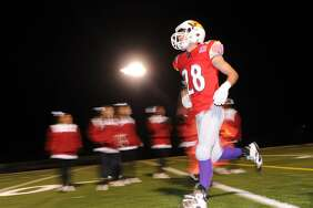 A Greenwich High football player takes to the field beneath the lights at Cardinal Stadium in Greenwich, Conn., Friday night, Oct. 28, 2016. With this year's later school day, and restrictions on use of lights at the school, darkness has become a problem for fall teams.