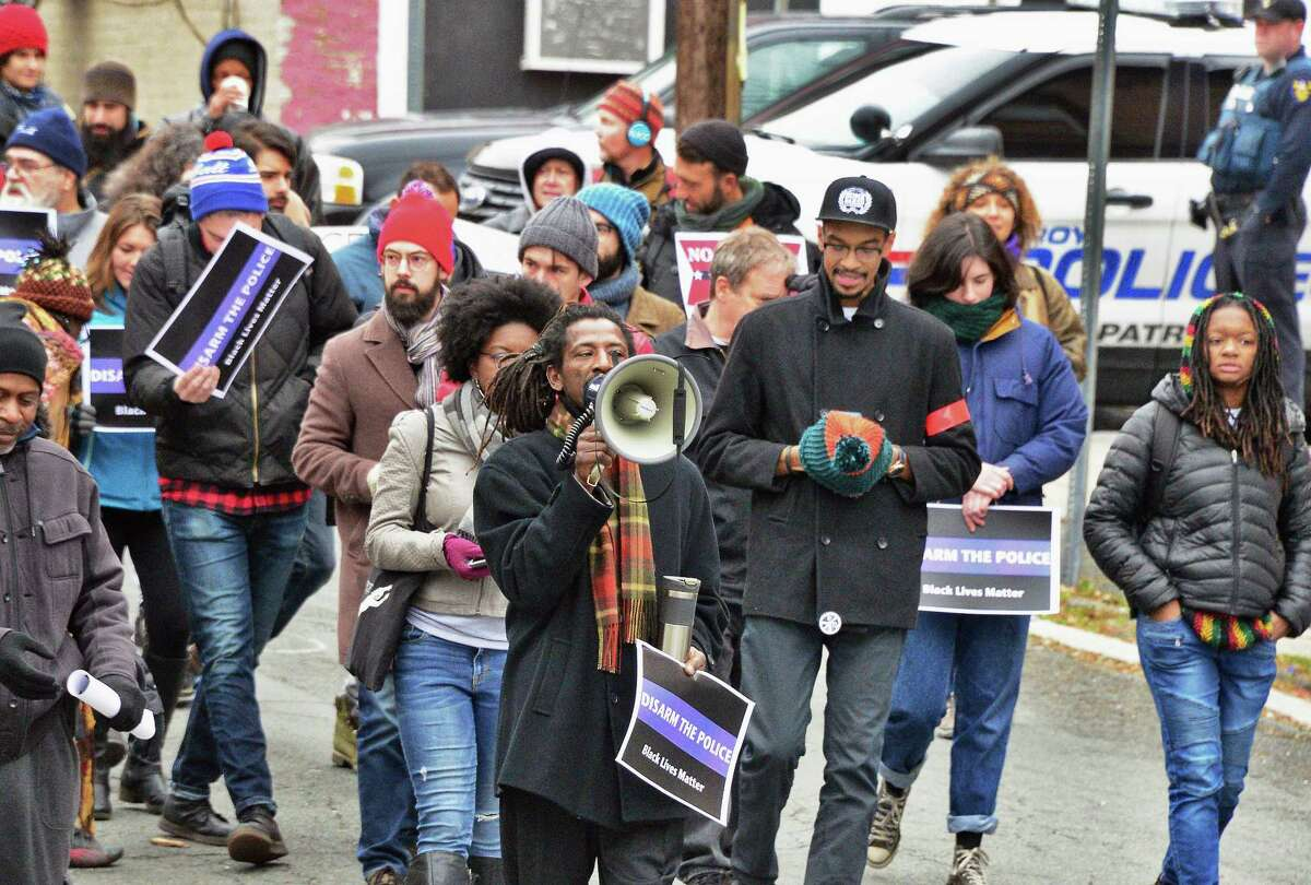 Dahmeek McDonald's uncle, identified only as Messiah,center, leads a rally to draw attention to the police killing of Edson Thevenin and shooting of Dahmeek McDonald and to call for the use of a civilian review board Saturday Nov. 18, 2017 in Troy, NY. (John Carl D'Annibale / Times Union)