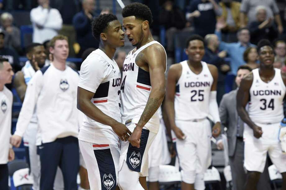 UConn's Alterique Gilbert, left, and Jalen Adams celebrate during the Huskies' win over Stony Brook. Photo: John Woike / Hartford Courant / Hartford Courant