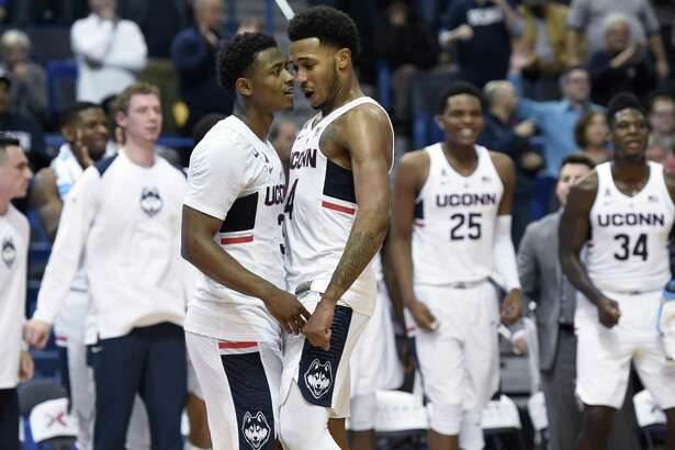 UConn's Alterique Gilbert, left, and Jalen Adams celebrate during the Huskies' win over Stony Brook.