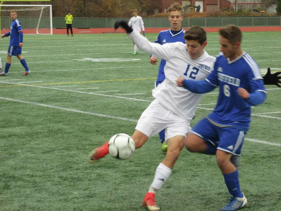 Lewis Mills' Matt Gilbert (12) and Suffield's David Swan (6) wage one of the game-long battles leading to the Spartans' first Class M boys soccer championship in 20 years Saturday morning at Willow Brook Park in New Britain. Photo: Peter Wallace / For Hearst Connecticut Media