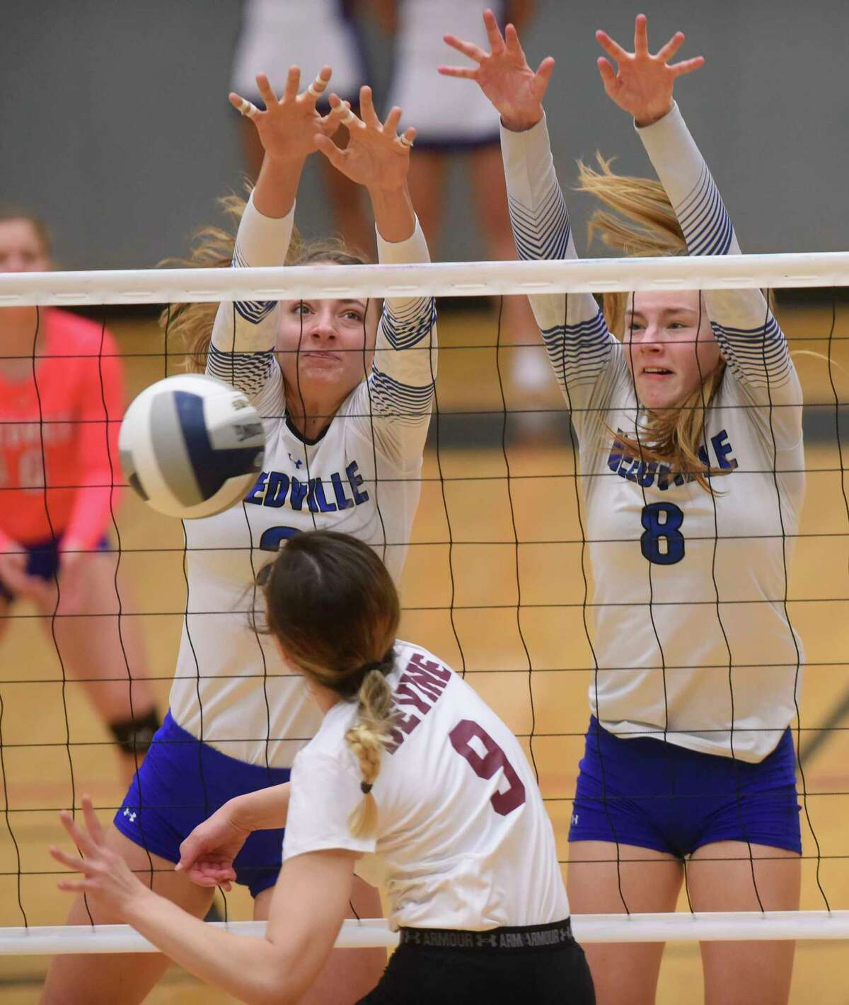 Needville's Sydney Sacra, left, and Madison Schultz (8) of Needville block a spike by Devine's Caimee Fowler (9) during UIL Region IV-4A volleyball playoffs action at Littleton Gym on Friday, Nov. 10, 2017.