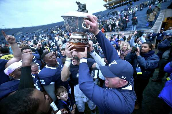 Spencer Rymiszewski (center) and Yale head coach Tony Reno hold the Ivy League Football Trophy after defeating Harvard 24-3 at the Yale Bowl in New Haven on November 17, 2017.