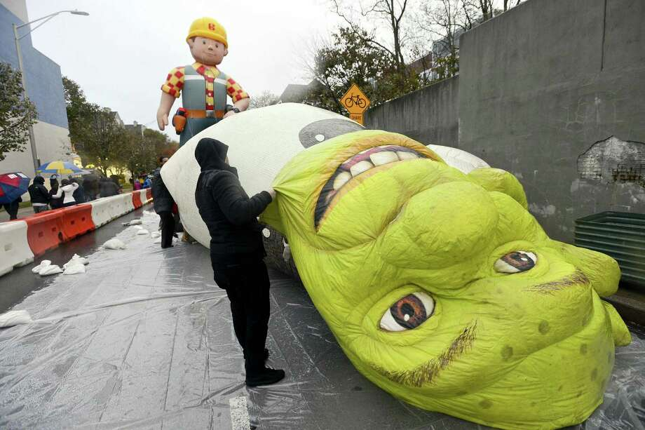 Workers unfold Shrek during an inflation party for the 24th annual Stamford Downtown Parade Spectacular presented by The Stamford Advocate in Stamford, Conn. on Saturday, Nov. 18, 2017. The pre-party event hosted by Point 72 Asset Management featured the inflation of 16 giant character balloons coming to life, D.J. music, dancing and a meet and greet with parade talent including clowns and cartoon characters. Photo: Matthew Brown / Hearst Connecticut Media / Stamford Advocate