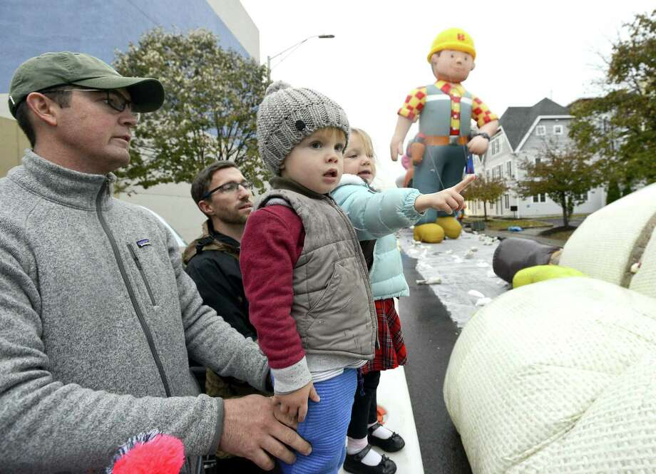 From left Matthew Haneline of Charlotte, North Carolina holds his son Mack as he and cousins Andrew Holbrook and daughter Evelynn watch a giant character balloons come to life during an inflation party for the 24th annual Stamford Downtown Parade Spectacular presented by The Stamford Advocate in Stamford, Conn. on Saturday, Nov. 18, 2017. The pre-party event hosted by Point 72 Asset Management featured the inflation of 16 giant character balloons, D.J. music, dancing and a meet and greet with parade talent including clowns and cartoon characters. Photo: Matthew Brown / Hearst Connecticut Media / Stamford Advocate