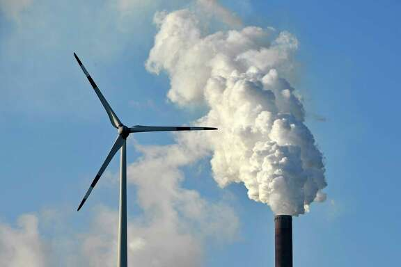 A coal-burning power plant steams behind wind generators in Gelsenkirchen, Germany. In Bonn, the global climate talks ended a two-week run Saturday morning after an all-night session.