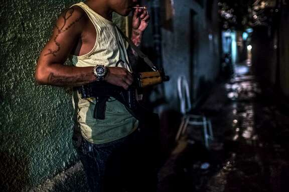 A drug gang soldier secures his post in northern Rio de Janeiro. As more neighborhoods fall under the control of gangs, violence increases. This year in Rio, 119 police officers have been killed. Last year, there were 61,619 people killed across Brazil, making it the deadliest year on record.
