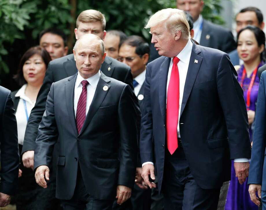 U.S. President Donald Trump, right, and Russia's President Vladimir Putin talk during the family photo session at the APEC Summit in Danang, Vietnam Saturday, Nov. 11, 2017. Trump and Putin may not be having a formal meeting while they're in Vietnam for an economic summit. But the two appear to be chumming it up nonetheless. Snippets of video from the Asia-Pacific Economic Cooperation conference Saturday have shown the leaders chatting and shaking hands at events including a world leaders' group photo. (Jorge Silva/Pool Photo via AP) Photo: Jorge Silva, POOL / Pool Reuters