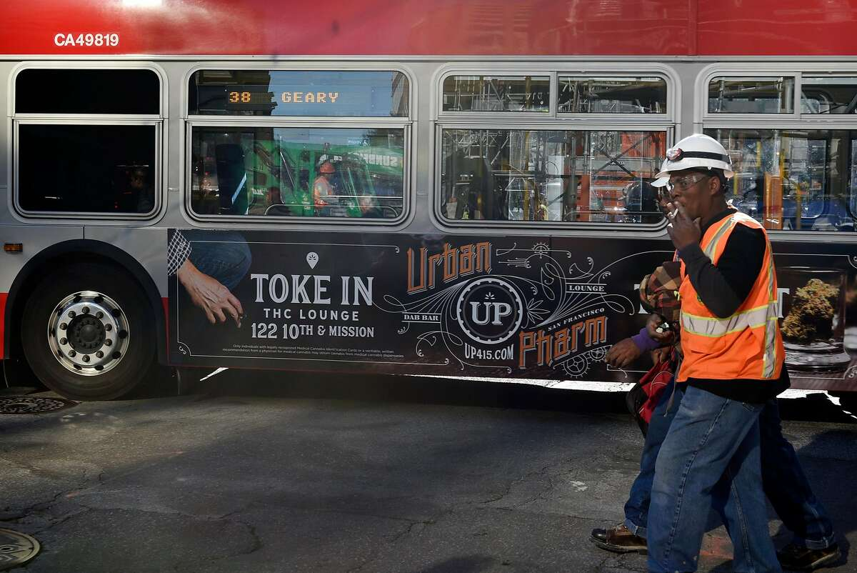 Pedestrians walk past an advertisement for Urban Pharm marijuana dispensary is seen on the side of a MUNI bus in downtown San Francisco, CA, on Friday November 17, 2017.