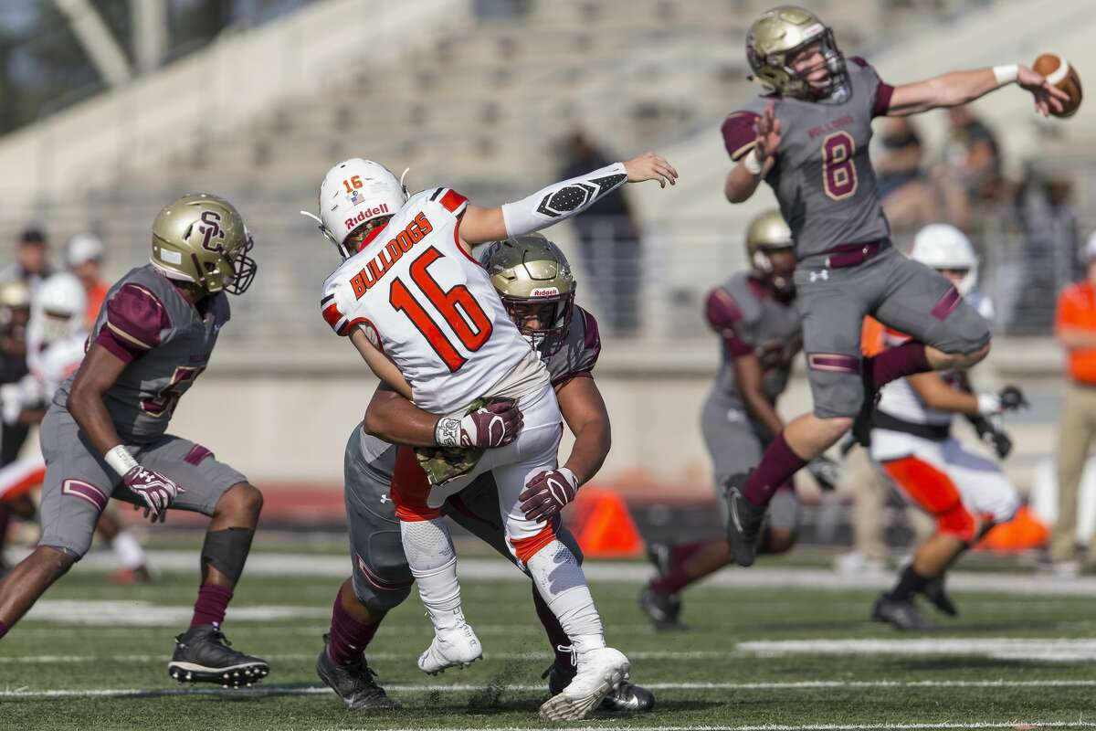 La Porte Bulldogs Brett Bihm (16) is hit after a pass by Summer Creek Bulldogs John Goree (44) in the first half of a November game. Goree signed a national letter of intent to play for Houston Baptist.