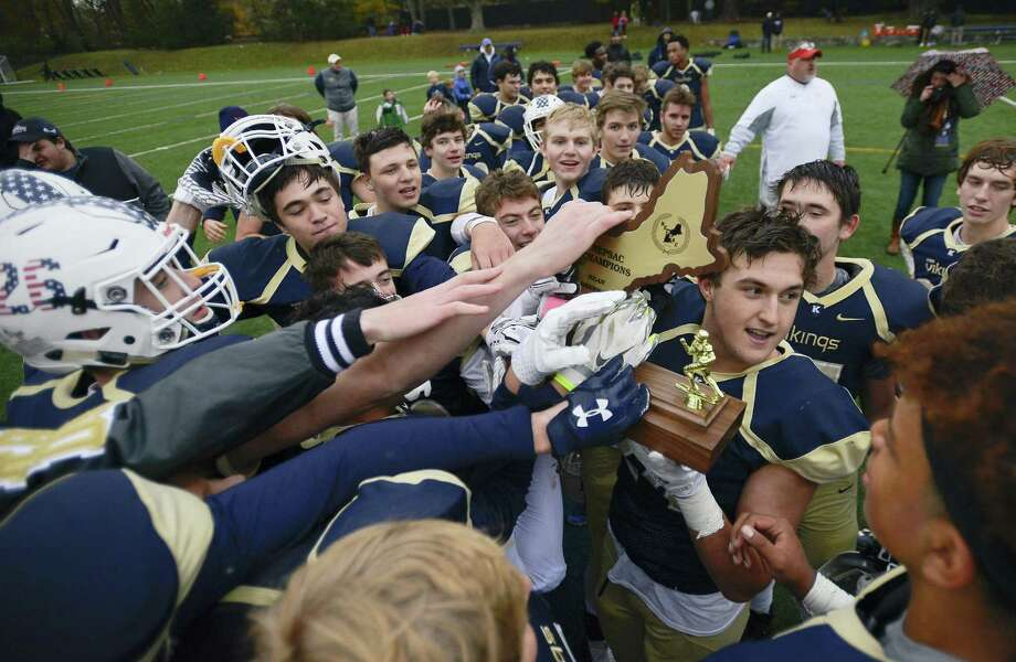 King Kelly Gouin holds the championship trophy as the Vikings celebrate their win over Portsmouth Abbey during the Sean Brennan Bowl of the NEPSAC Class C football championship in Stamford, Conn. on Saturday, Nov. 18, 2017. King defeated Portsmouth Abbey 27-6 to capture their second straight New England football title. Photo: Matthew Brown / Hearst Connecticut Media / Stamford Advocate