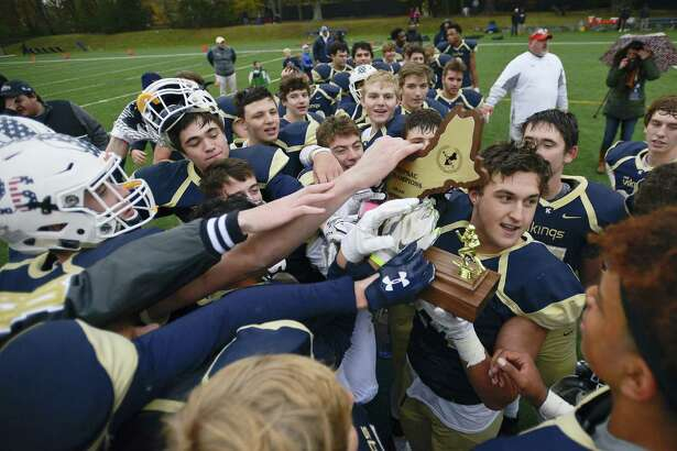 King Kelly Gouin holds the championship trophy as the Vikings celebrate their win over Portsmouth Abbey during the Sean Brennan Bowl of the NEPSAC Class C football championship in Stamford, Conn. on Saturday, Nov. 18, 2017. King defeated Portsmouth Abbey 27-6 to capture their second straight New England football title.