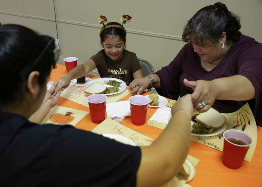 Vaness Rodriquez, 8, says Grace with her mother, Elvira Rodriguez, left, and grandmother, Virginia Rosas, before they have a meal at community thanksgiving dinner at Veterans of Foreign Wars Hall on Saturday, Nov. 18, 2017, in Dickinson. ( Yi-Chin Lee / Houston Chronicle ) Photo: Yi-Chin Lee, Houston Chronicle / © 2017  Houston Chronicle