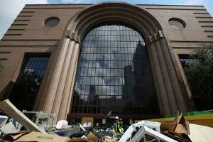 Construction workers toss bags of trash into a dumpster outside the Wortham Theater Center, which was severely damaged by flooding during Tropical Storm Harvey Tuesday, Sept. 19, 2017, in Houston. ( Godofredo A. Vasquez / Houston Chronicle )