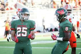 The Woodlands' Bryeton Gilford (25) celebrates with Malik Johnson (8) after scoring a touchdown during the varsity football game on Friday,  Nov. 17, 2017, at Woodforest Bank Stadium. (Michael Minasi / Houston Chronicle)