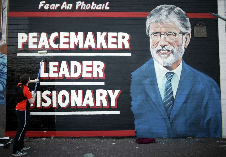 FILE - In this Friday, May, 2 2014 file photo, a man adds the finishing touch to a newly painted mural of Gerry Adams on the Falls Road, West Belfast, Northern Ireland. Gerry Adams has announced that he plans to step down as leader of Sinn Fein next year after heading the party for over 30 years. Adams said in a speech at the party's annual conference in Dublin on Saturday, Nov. 18, 2017 that he will not stand for the next Irish parliamentary election. (AP Photo/Peter Morrison, file) Photo: Peter Morrison, STR / Copyright 2017 The Associated Press. All rights reserved.