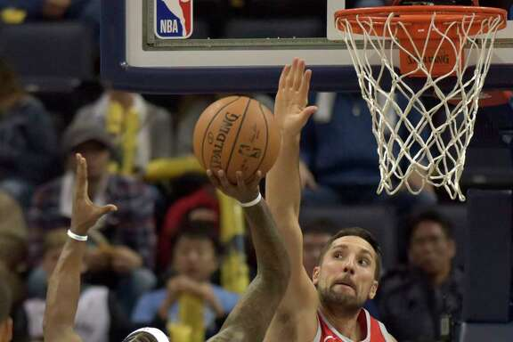 Rockets forward Ryan Anderson, right, puts up a stout line of defense against  Grizzlies guard Mario Chalmers' fall-away jumper in the first half.