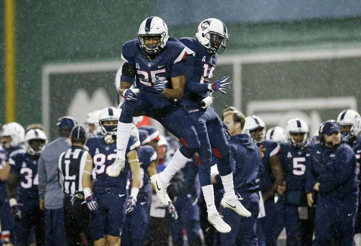 UConn defensive backs Tyler Coyle (25) and Tahj Herring-Wilson (14) celebrate after a stop against Boston College on Saturday.