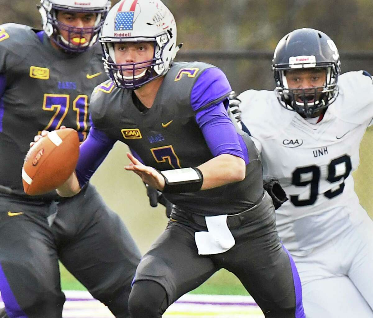 UAlbany quarterback #7 Will Brunson, center, scrambles away from New Hampshire's #99 Brian Carter during their Colonial Athletic Association game Saturday Nov. 18, 2017 in Albany, NY. (John Carl D'Annibale / Times Union)