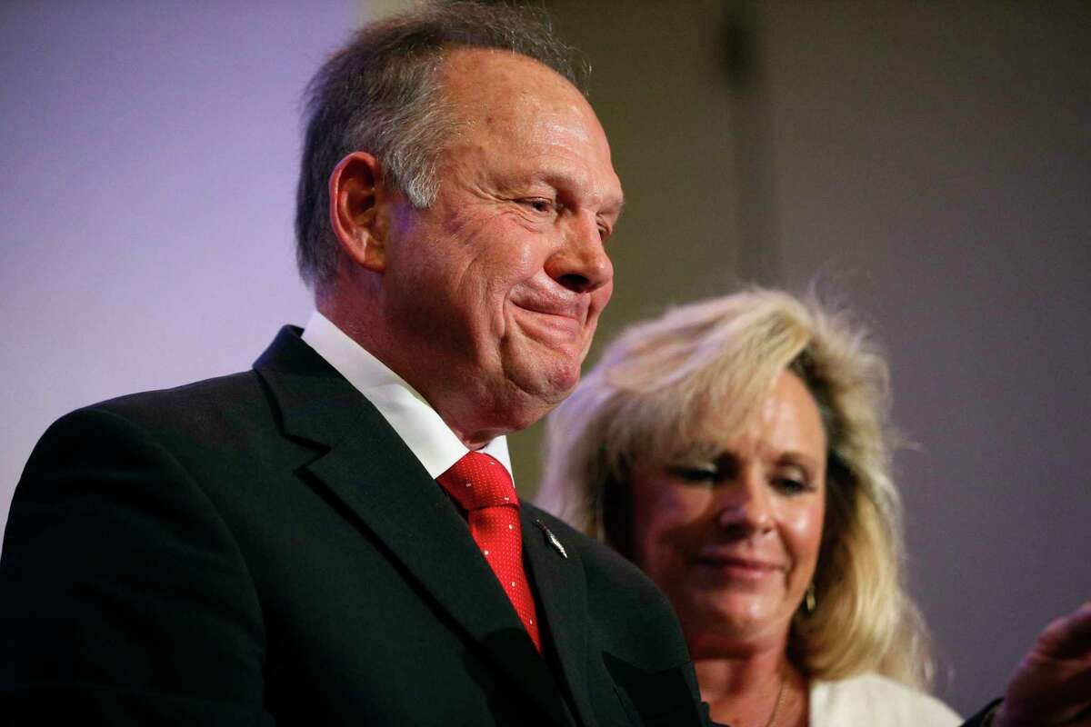 In this Nov. 16, 2017, photo, former Alabama Chief Justice and U.S. Senate candidate Roy Moore speaks at a news conference in Birmingham, Ala., with his wife Kayla Moore, right. A sex scandal has relegated Moore's hard-line positions on LGBT issues to the background in Alabama's turbulent Senate race even as religious activists blame the
