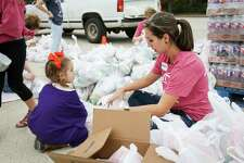 Volunteer Andrea Kinder and her daughter Kylee, 3, help separate groceries into bags during the Thanksgiving Grocery Giveaway event on Friday at the Ark Church in Conroe.
