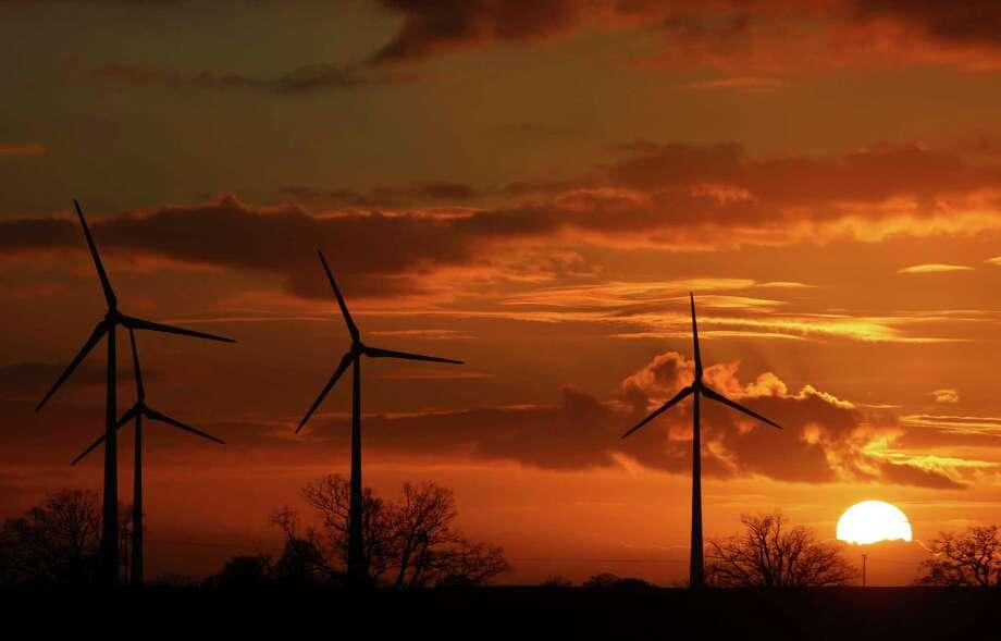 The sun sets behind wind turbines near Pokrent, northern Germany, Friday, Nov. 17, 2017. (Jens Buettner/dpa via AP) ORG XMIT: DSOB102 Photo: Jens Buettner / dpa-Zentralbild